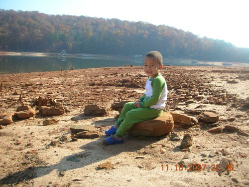 """My youngest at 2, sitting on the """"beach"""" at the lakehouse."""