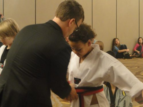 The owner of the studio tying on her new black belt after 3 hours of testing.