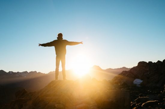 Figure standing on mountain top with sun setting in background